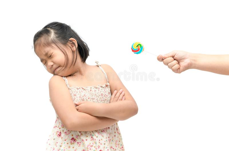 Girl with expression of disgust against candy and suffering from. Asian child girl with expression of disgust against candy and suffering from toothache isolated stock photo