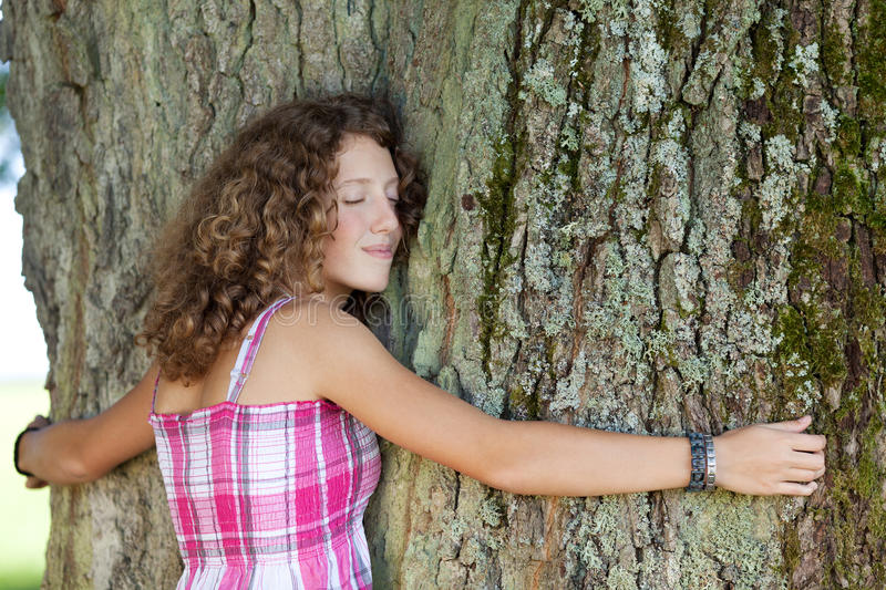 Girl With Eyes Closed Embracing Tree. Side view of teenage girl with eyes closed embracing tree at park stock photo