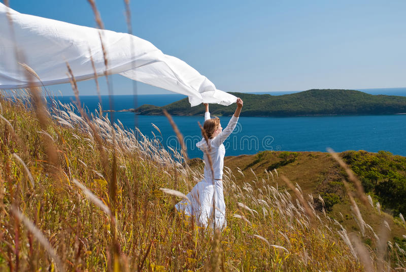 Girl with fabric in hands in the wind royalty free stock images