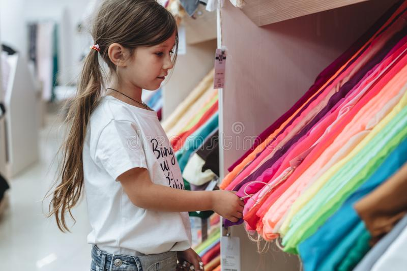 Girl in a fabric store chooses a multi-colored fabric royalty free stock images