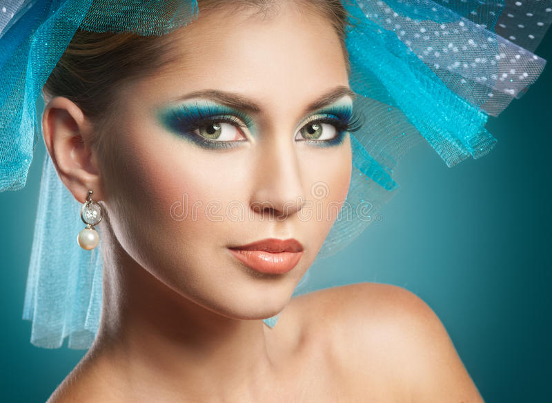 Girl face. Beautiful woman with blue make-up royalty free stock image