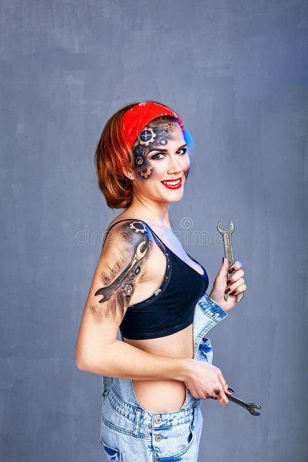 Girl with face art mechanic holding spanner and smiling. stock images