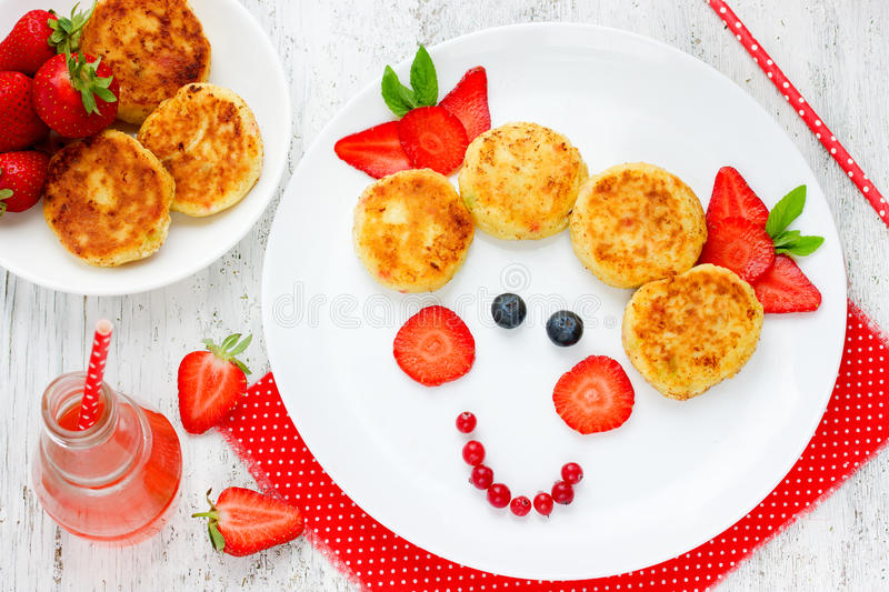 Girl face dessert or breakfast for of kids - cheese pancakes wit. H berries on white table top view stock photos
