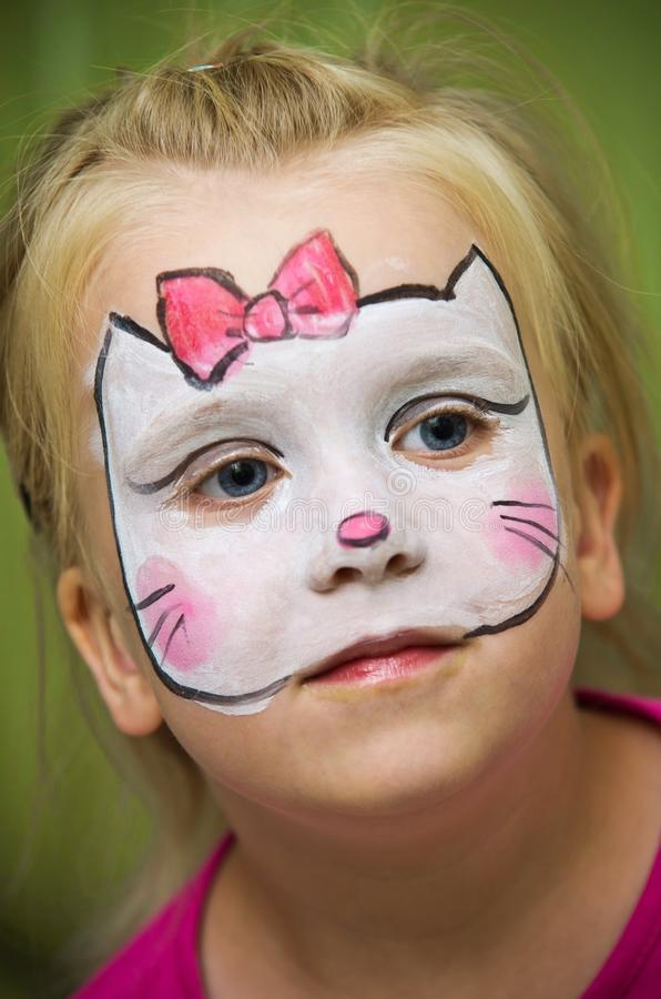 Girl with face painted. A little cute girl with her face painted with in an image of a cat or kitten stock images