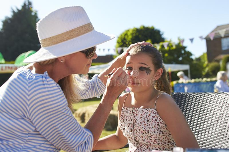 Girl At Face Painting Stall At Summer Garden Fete royalty free stock images