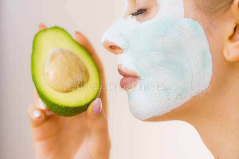 Girl facial mud mask holds avocado fruit. Young woman with white green mud mask on face holding avocado fruit. Teen girl taking care of her skin, cleaning the stock images