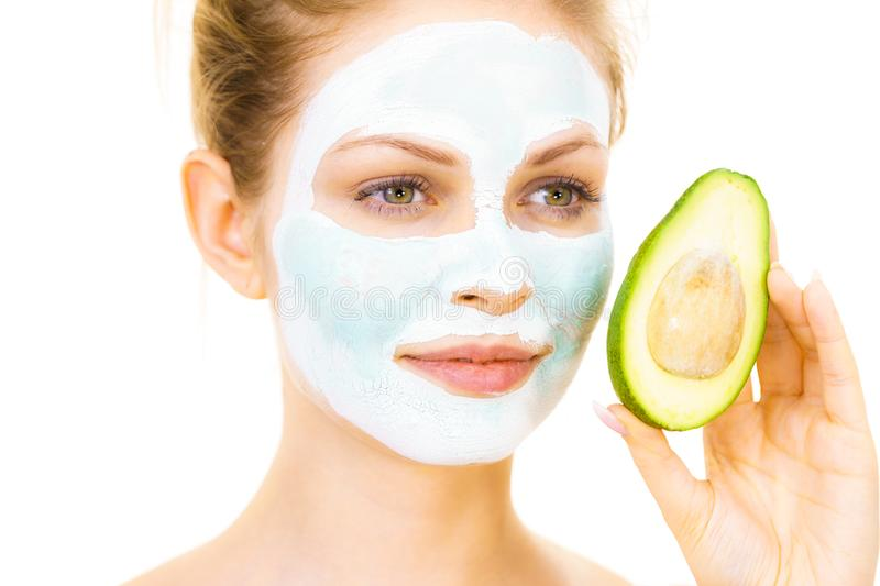 Girl facial mud mask holds avocado fruit. Young woman with white green mud mask on face holding avocado fruit. Teen girl taking care of her skin, cleaning the royalty free stock image
