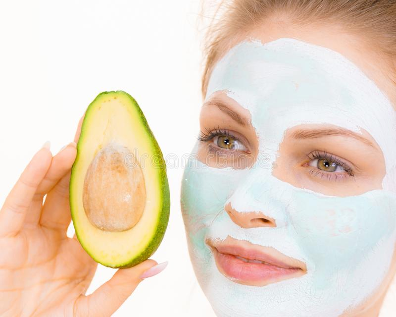 Girl facial mud mask holds avocado fruit. Young woman with white green mud mask on face holding avocado fruit. Teen girl taking care of her skin, cleaning the royalty free stock images