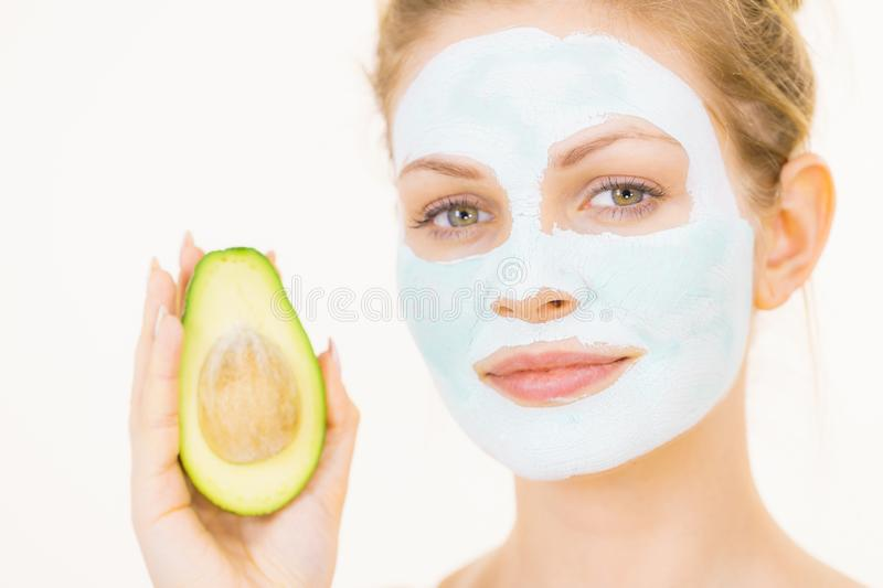 Girl facial mud mask holds avocado fruit. Young woman with white green mud mask on face holding avocado fruit. Teen girl taking care of her skin, cleaning the stock photography