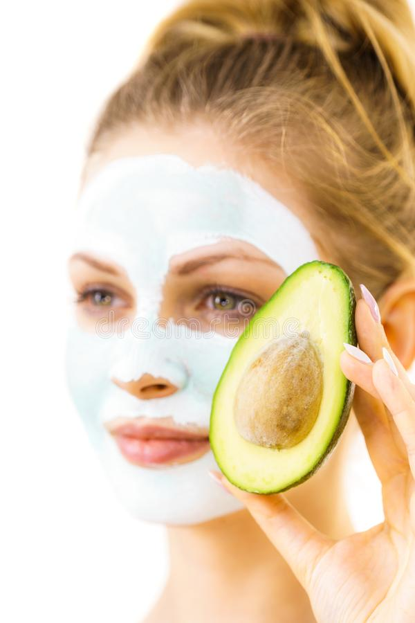 Girl facial mud mask holds avocado fruit. Young woman with white green mud mask on face holding avocado fruit. Teen girl taking care of her skin, cleaning the stock image