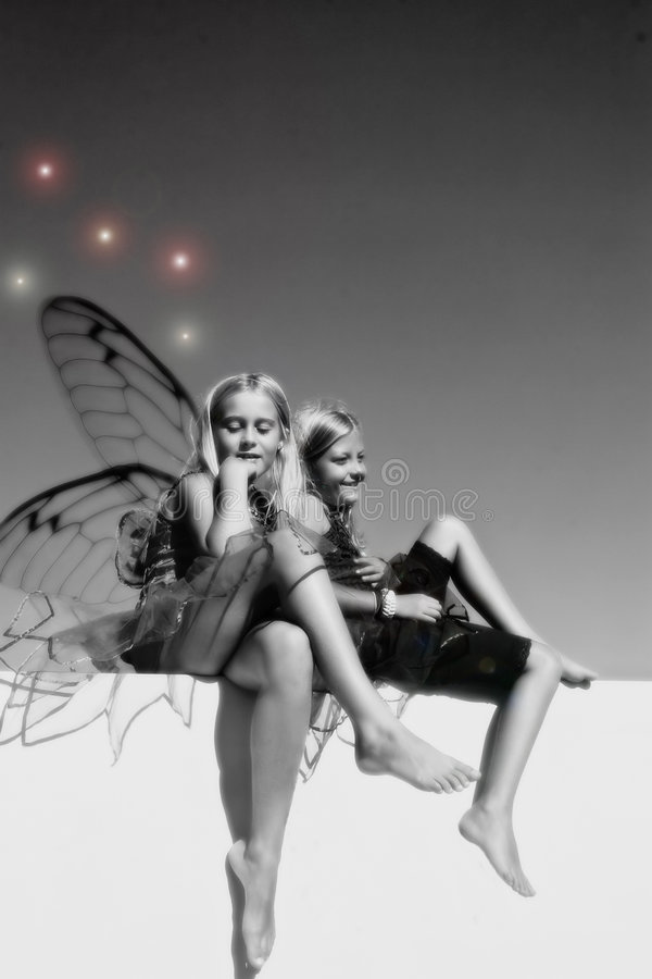 Girl Fairies. Black and white image of two girl fairies sitting on a wall royalty free stock photography