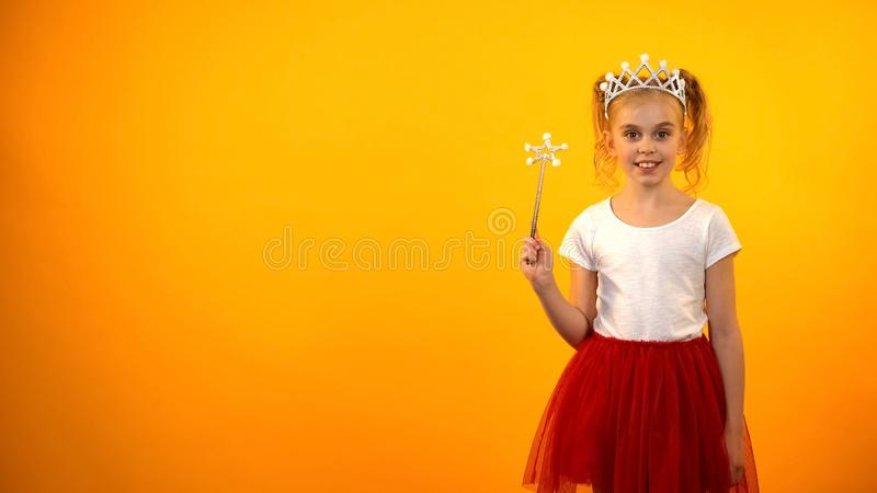 Girl in fairy costume holding magic wand and looking to camera, little princess stock images