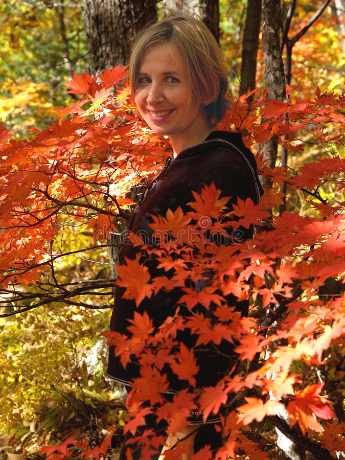 girl in fall maple leaves stock photo
