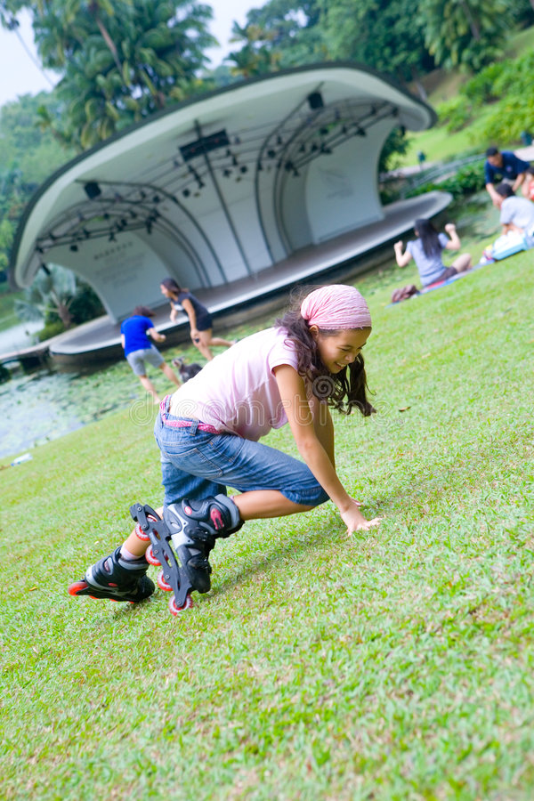 Girl falls while roller blading in the park. Young girl enjoys roller blading in the park stock images