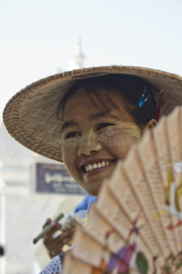 Girl with a fan. Burmese girl smiling. Beautiful girl smiling in a littlle village in Myanmar royalty free stock image
