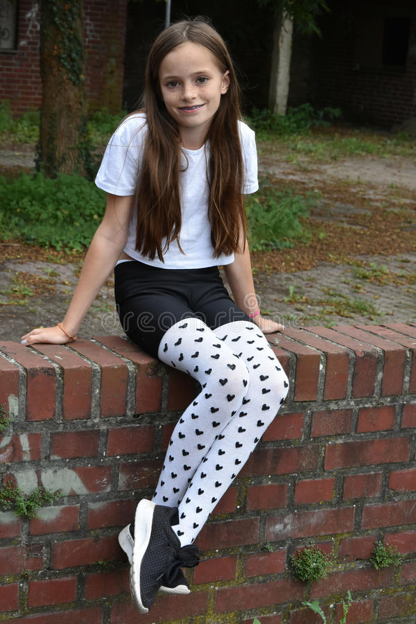 Girl with fancy pair of tights. Teenage girl with fancy pair of tights with little black hearts stock images