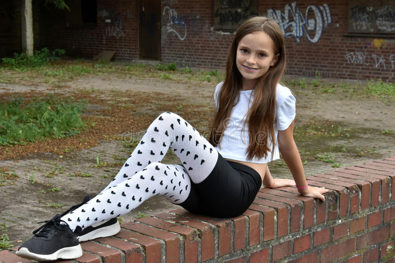 Girl with fancy pair of tights. Teenage girl with fancy pair of tights with little black hearts royalty free stock photos