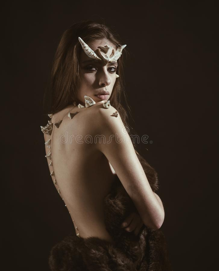 Girl with fantasy style make up. Woman with thorns on back shoulders looks like fantasy creature. Halloween ideas. Concept. Girl with thorns devil dragon royalty free stock photos