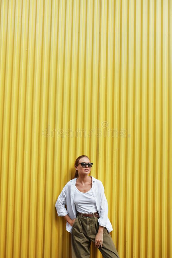 Girl. Fashion Portrait Of Beautiful Woman. Stylish Model In Casual Clothes And Sunglasses Standing Against Yellow Metal Fence. Low Angle Shot Of Female In royalty free stock photography
