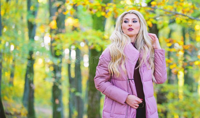 Girl fashionable blonde walk in autumn park. Autumn hair care concept. Autumn hair care is important so as to avoid dry. Frizzy hair. Cold blonde concept. How royalty free stock image