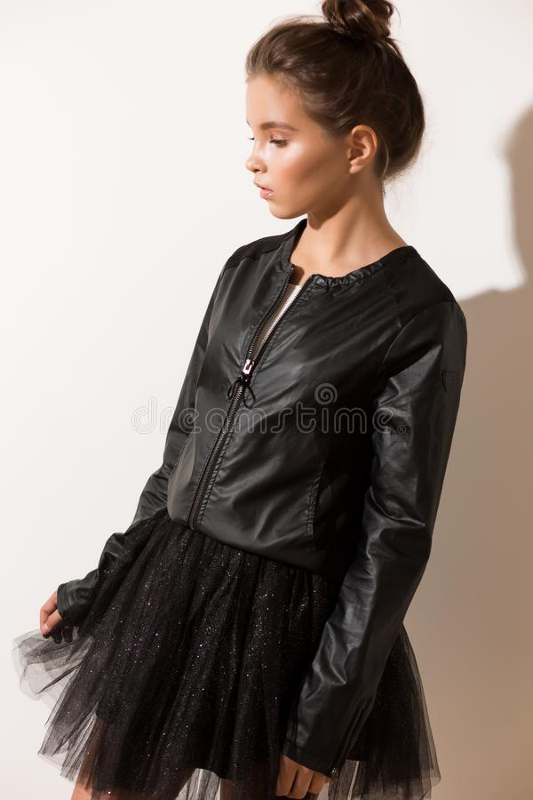 Girl in fashionable clothes, fluffy skirt, black jacket. A girl in a black jacket and a full skirt is standing near a white wall royalty free stock image