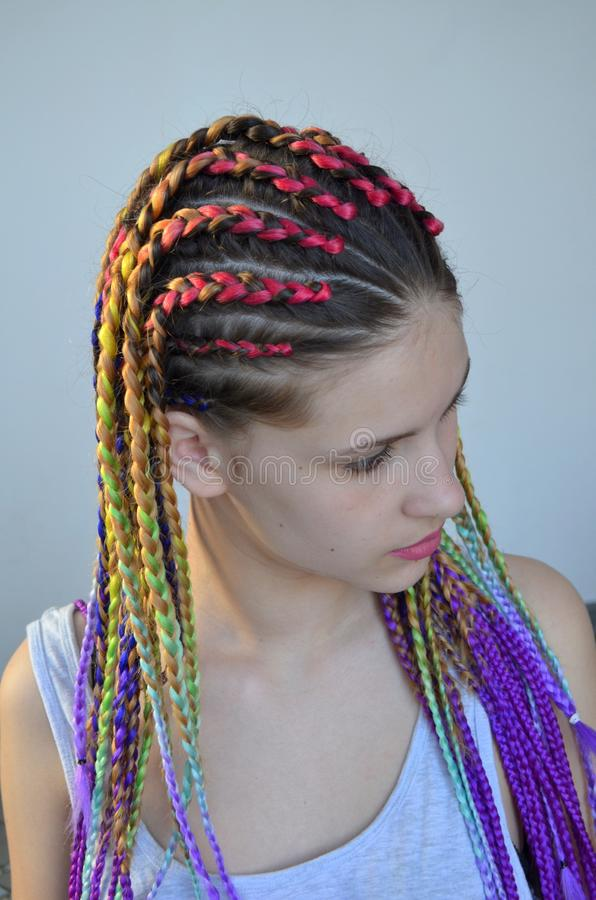 A girl with a fashionable set of multicolored braids Kanekalon. Colored artificial strands of hair. Material for plaiting braids. Mastery of weaving from hair stock image
