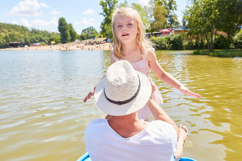 Girl with father in the boat on a trip. Little girl with father on a tour in the boat on a lake in summer royalty free stock photos