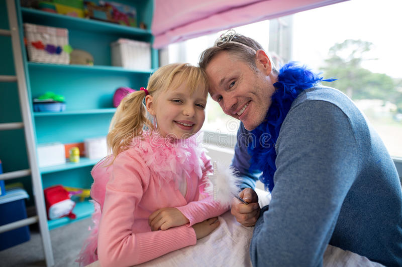Girl and father dressed as fairy sitting head to head stock photo