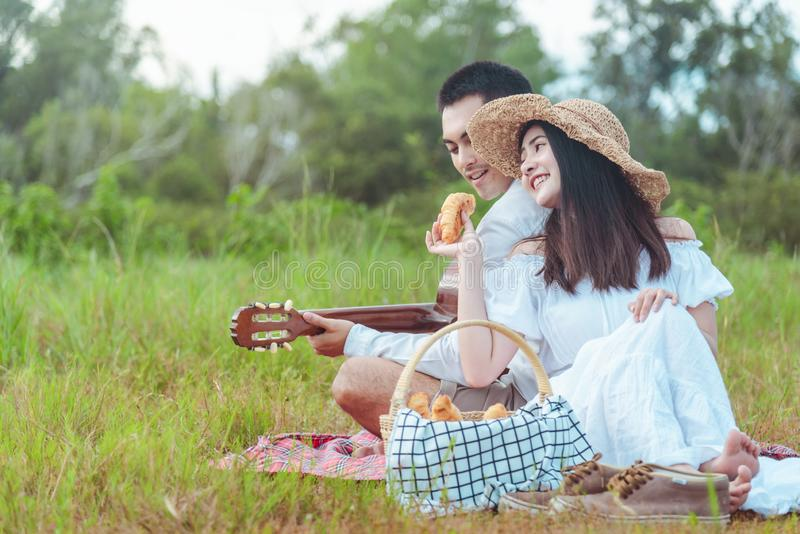 Girl feeding apple to her boyfriend on a picnic while he is playing on a guitar royalty free stock photography