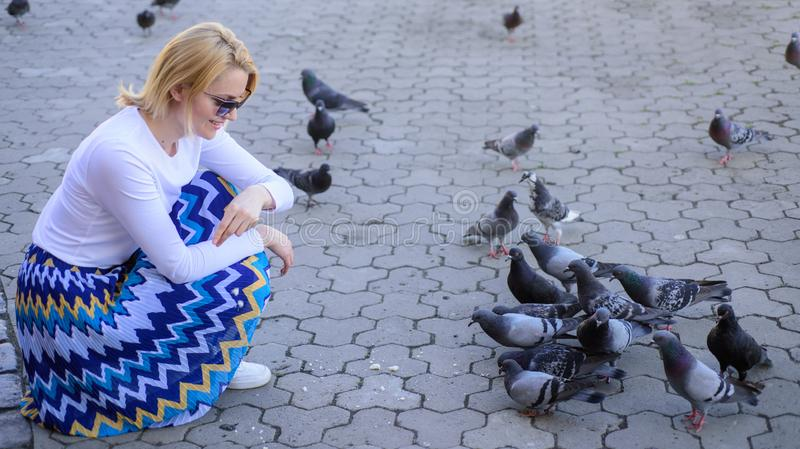 Girl feeding dove birds. Group doves on city square waiting treats. Share generosity. Girl blonde woman relaxing city stock image