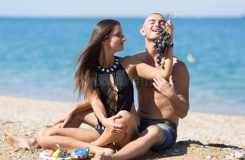 Girl feeds guy with black grapes on beach royalty free stock images