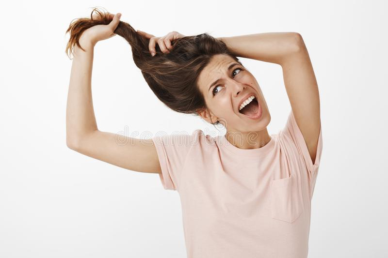 Girl feeling annoyed as trying comb unruly hair pulling strands with raised hands screaming from pain and discomfort royalty free stock photography