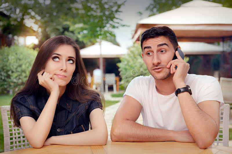Girl Feeling Bored while her Boyfriend is on The Phone. Woman and men on a boring date ignoring rules of politeness stock photos