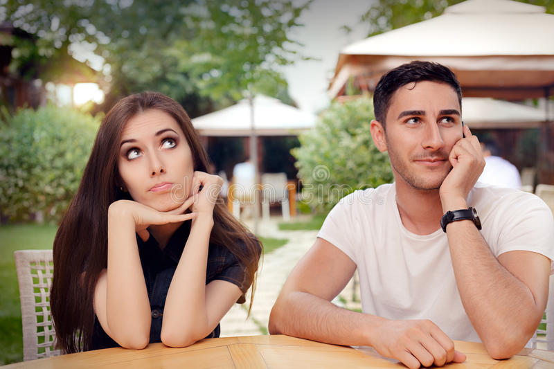 Girl Feeling Bored while her Boyfriend is on The Phone. Woman and men on a boring date ignoring rules of politeness stock photo