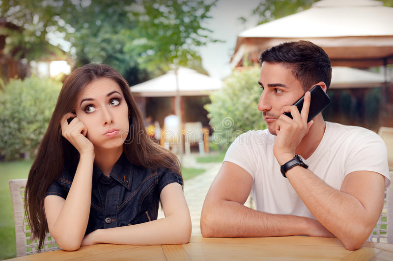 Girl Feeling Bored while her Boyfriend is on The Phone. Woman and men on a boring date ignoring rules of politeness stock images
