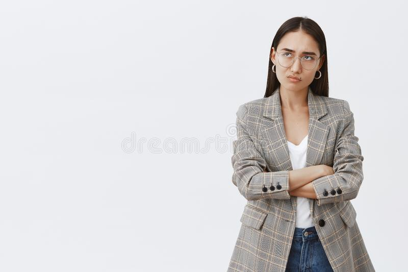 Girl feeling displeased being disappointed with ruined plans. Gloomy and moody cute adult woman in glasses and jacket. Smirking and sulking, frowning from royalty free stock photo