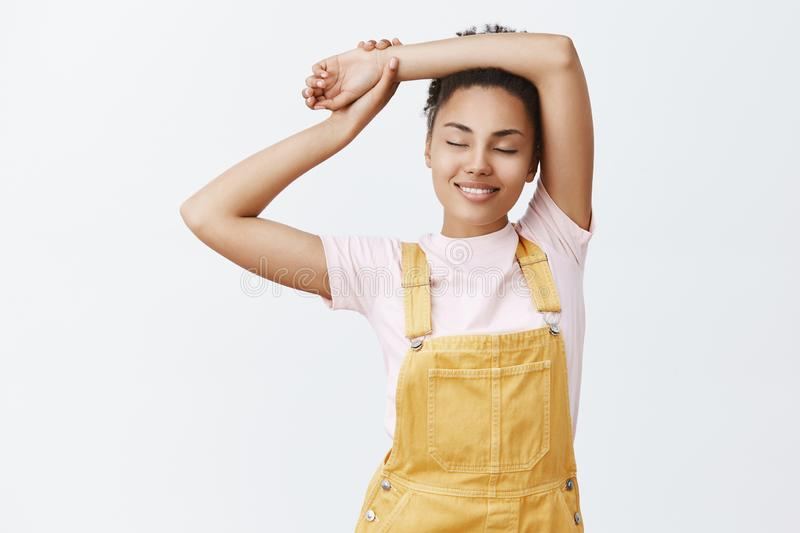 Girl feeling great after meditation. Portrait of calm and relaxed feminine dark-skinned woman in stylish yellow royalty free stock photo