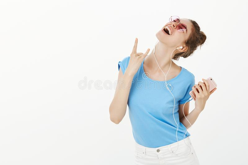 Girl feeling like on live concert while listening music in brand new earphones. Excited carefree woman in sunglasses stock images
