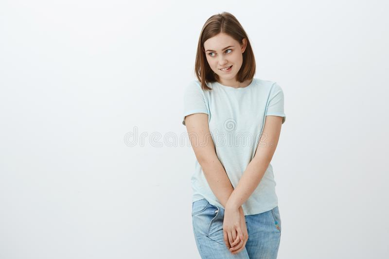 Girl feeling shy standing near love interest. Awkward timid and insecure cute young girl biting lower lip turning gaze royalty free stock image