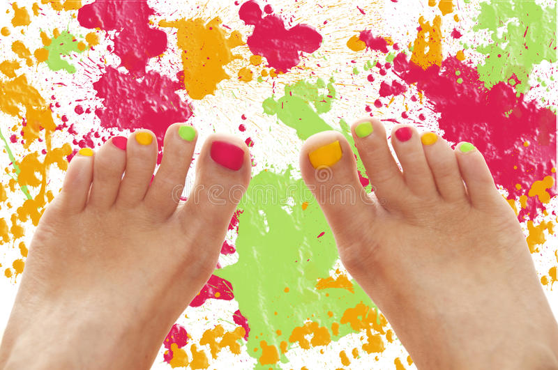 Girl feet with rainbow colorful nails stock image