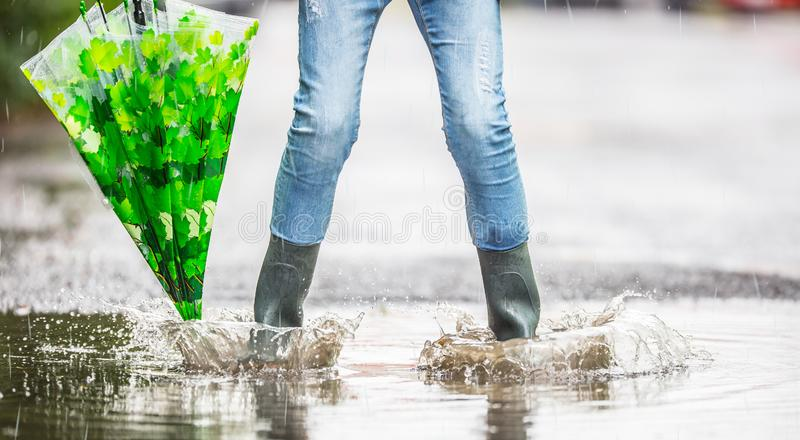 Girl feet in rubber boots with umbrella under rain in puddle stock photo