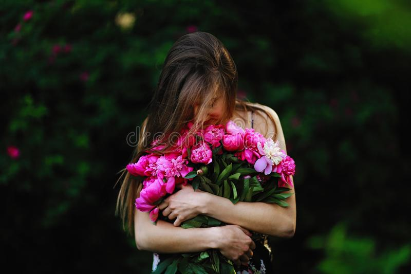 Girl in the field of flowers. girl hugs a bouquet with flowers. Bouquet of Peony royalty free stock photography