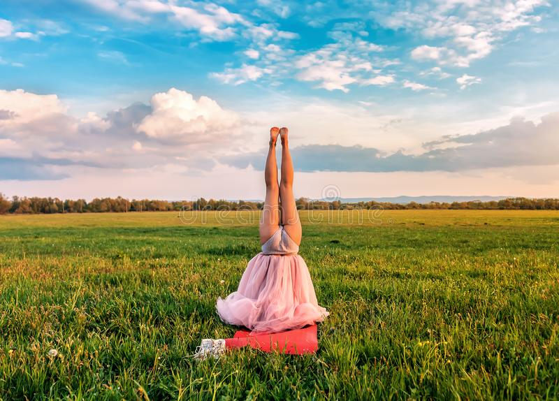 Girl in the field stands on the head stock photography