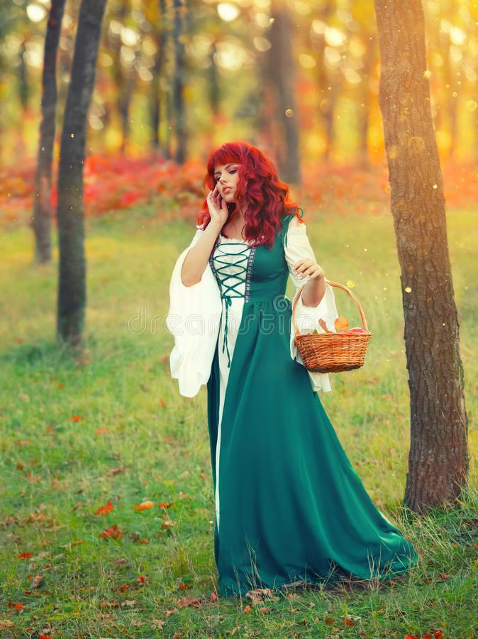 Girl with fiery red hair, an unusual appearance, in an emerald white gorgeous delightful dress, holds a basket and stock images