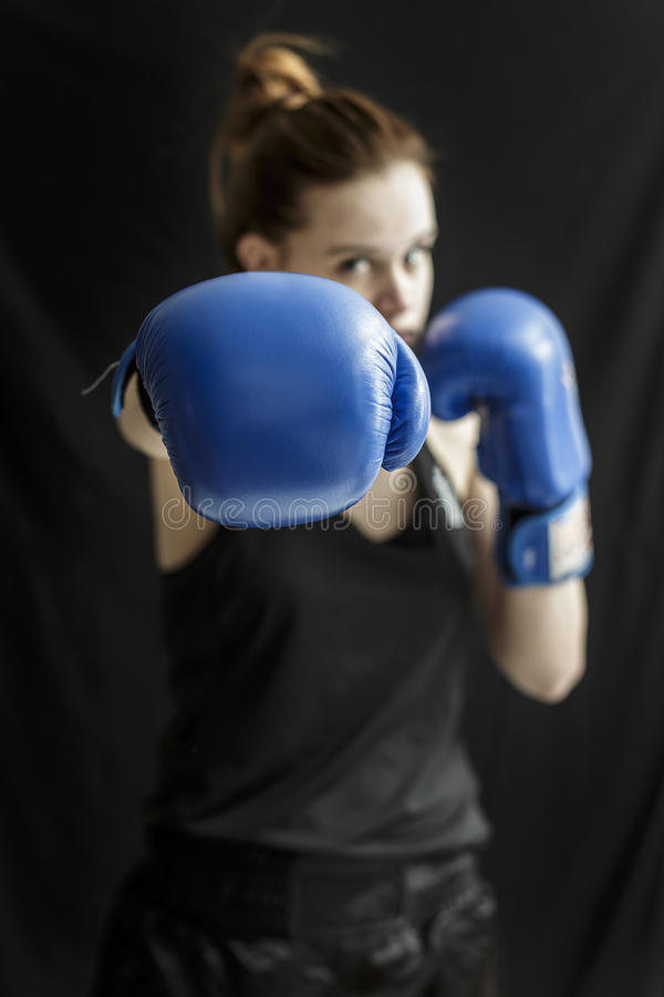 Girl fighter in blue boxing gloves stock photography
