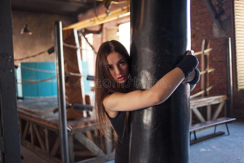 Girl fighter Boxing with punching bag, a young woman trains in the gym. stock photos