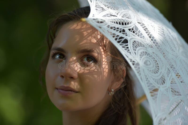 Girl with a filigree umbrella. Portrait of a girl with a filigree umbrella stock photo
