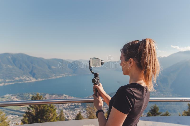 Girl filming with gimbal in the mountains over lake maggiore stock image