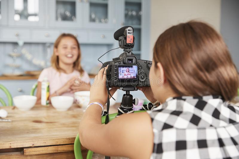 Girl filming her friend for cookery video blog in kitchen stock photography