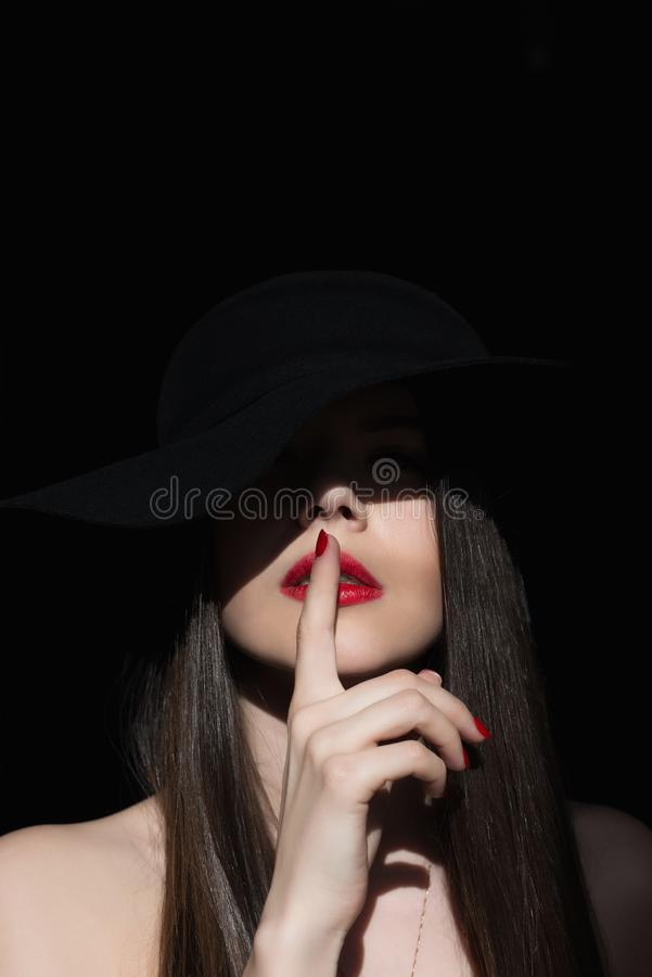 Girl with a finger at the mouth. A symbol of silence. The ray of the sun lights the girl in the dark. stock images